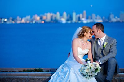 Bride and Groom sitting with San Diego skyline behind them at Admiral Kidd