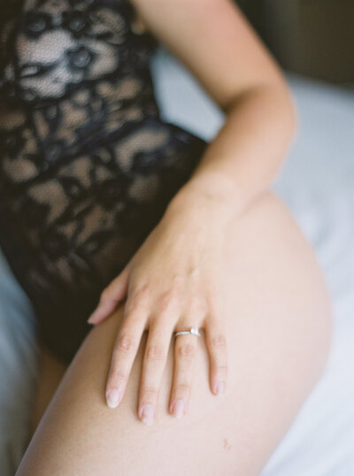 Boudoir image of woman leaning on bed with hand resting on leg