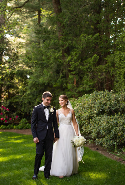 Bride and groom walking in flower garden in west hartford