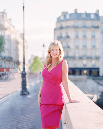 Photographer Cari Long stands by a bridge rail in pink dress in Paris