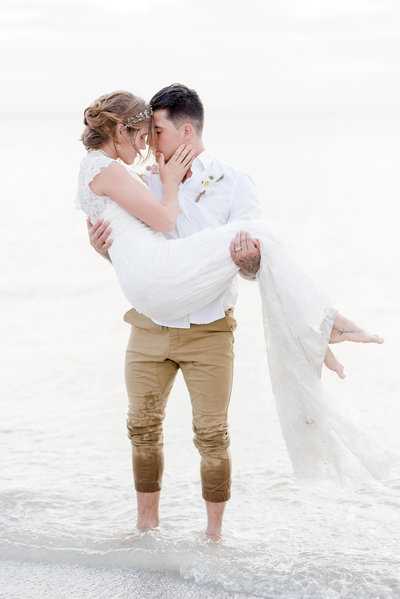 Groom carries bride through the surf of the ocean
