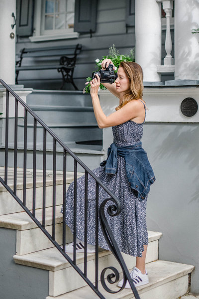 woman standing on stairs taking a picture while wearing a blue dress