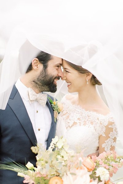 bride and groom laughing together under veil