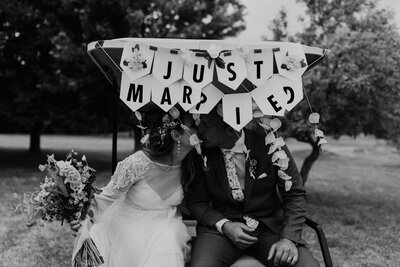 bride and groom kissing under a just married sign