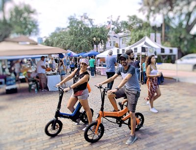 Married couple cruising around on there Blue Go-Bike M3 & Orange Go-Bike M4 at a local festival