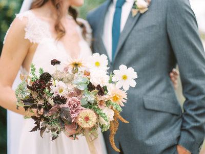 Bride and groom embrace while holding beautiful wedding bouquet