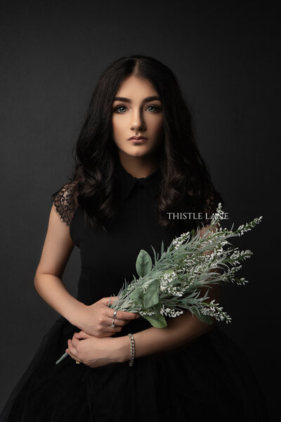 Beautiful girl in black gown with flowers