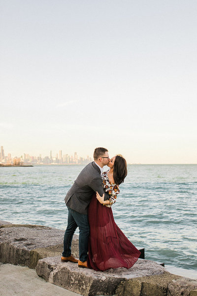 Couple dip and kiss at Chicago's Promontory Point for an engagement photo.