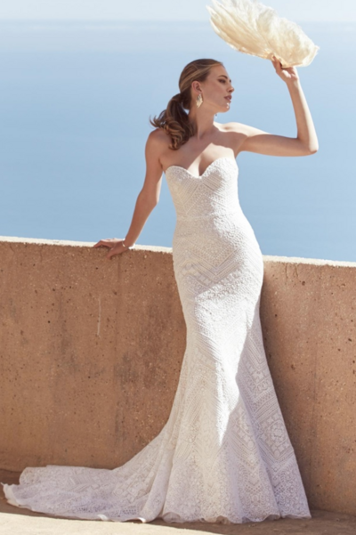 This gown made of luxe Gilda lace fits the figure then flares to a fluted hem that will elegantly trail behind you as you walk down the aisle.