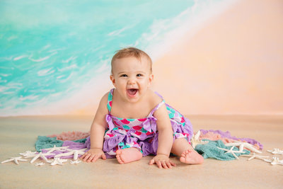 baby girl smiles in front of a beach themed backdrop