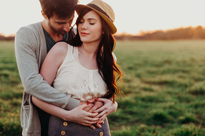 couple embrace in field during couples photoshoot