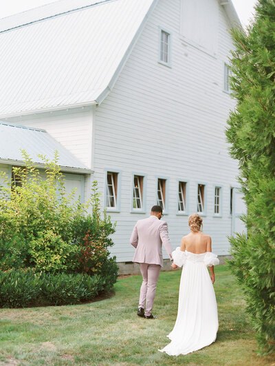 groom in a pastel purple suit holding bride's hand and walking away to their wedding reception