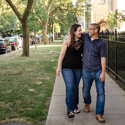 Couple walks down the sidewalk, laughing at one another, in the Ravenswood neighborhood of Chicago
