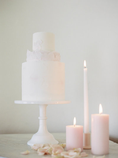 White and light pink wedding cake with decor that looks like rose petals