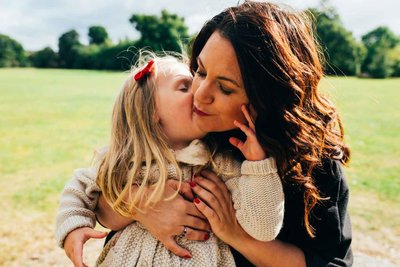 Relaxed photograph of mum and daughter kissing in Ipswich Christchurch Park