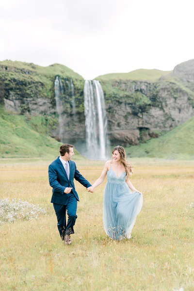 Sam and Petie,  owners of The Tuckers Photography, walk hand in hand in front of a waterfall in Iceland.
