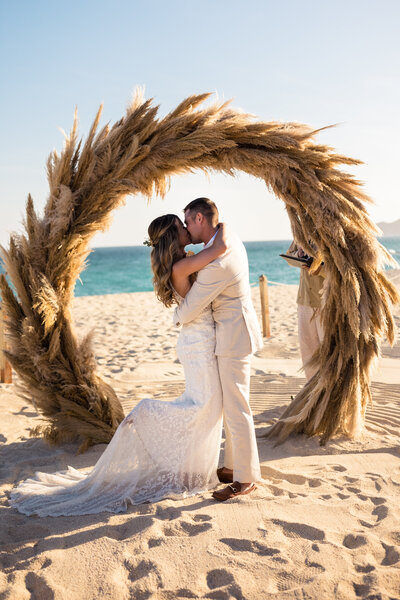 bride and groom kissing at beach wedding in cabo