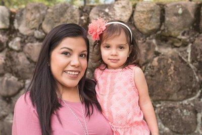 latin women in pink holding her daughter wearing a pink blow in her hair
