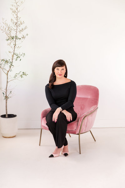 Headshot of woman sitting in pink chair