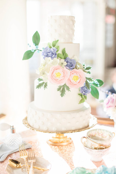white polka dot cake with large pink and blue flowers