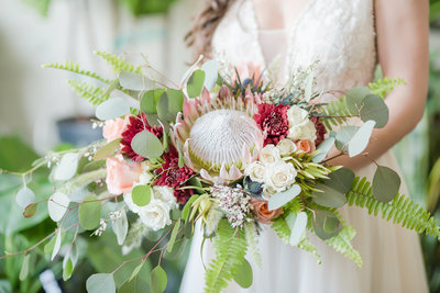 Bride holds stunning bouquet filled with colorful flowers and large protea