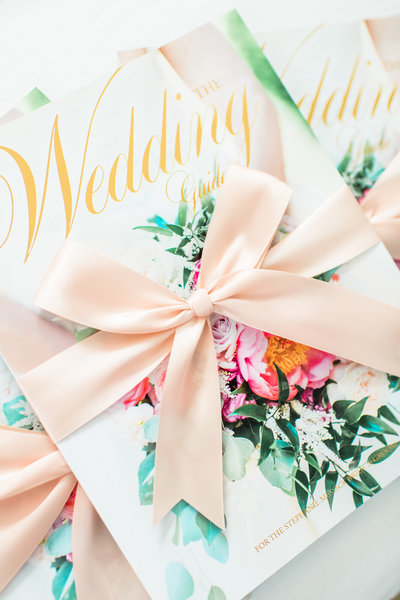 Pretty pink bow tied around a floral invitation.