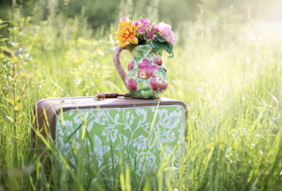 Flowers in a pitcher on top of a suitcase