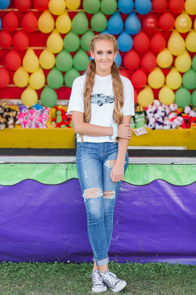 high school senior girl shigh school senior girl sitting  in front of ballon pop game at wayne county ohio fair photographed by Jamie Lynette Photography Canton Ohio Senior Photographer