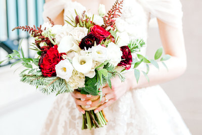 Bride holding red and green bouquet