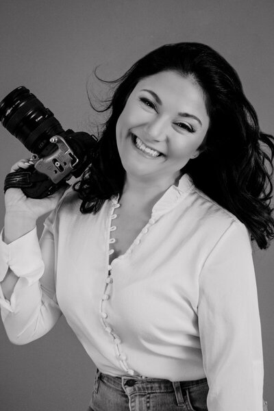 Black and white business headshot of Dana holding a camera