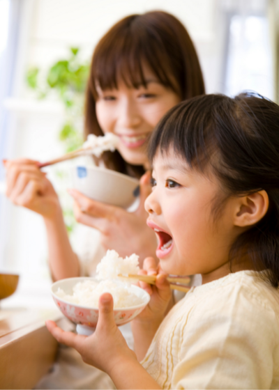 Thrive by Spectrum Pediatrics image for family mealtime coaching is a child happily eating with mother during mealtime