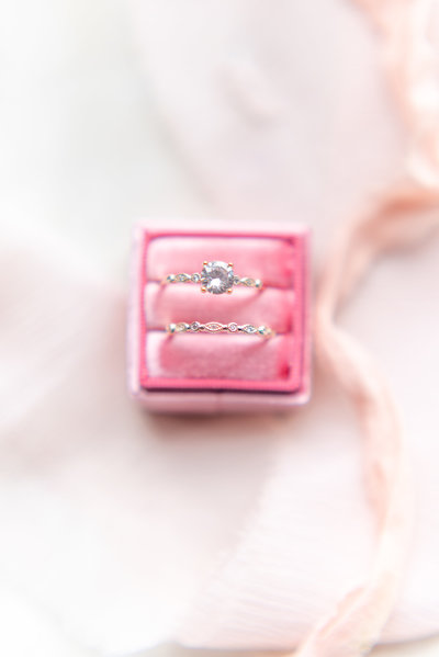 wedding ring in pink box surrounded by pink ribbon