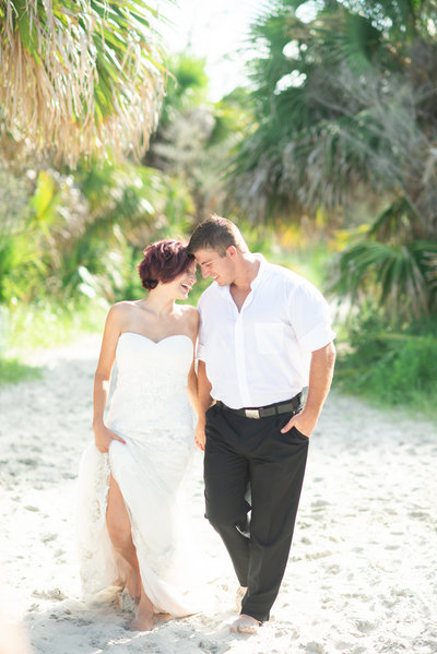 St Simons Island Wedding Day photographed by Megan Holley Photography- Couple is walking on the beach beneath the palm trees.