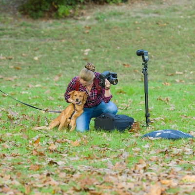 Photographer in grass with dog behind the scenes
