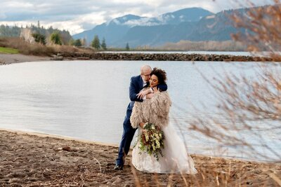 stylish bride and groom have intimate moment by columbia river gorge
