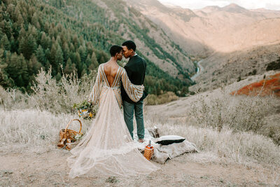 bride and groom embracing with mountains in the background
