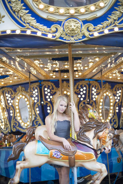 High school senior girl poses on a carousel