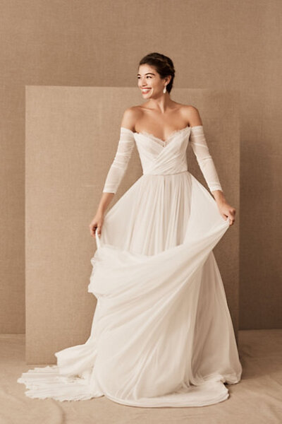If there were such a thing as an effortless wedding dress, this stretch mesh style would be it. With a full skirt and shirred sleeves, it's easy on the eyes—and equally easy to wear.