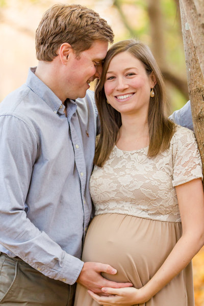 Husband embraces his smiling wife as she embraces her pregnant belly during maternity photo shoot