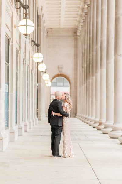 couple hugging in columned walkway