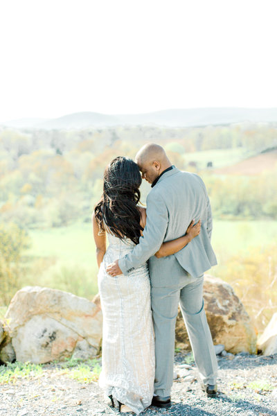 Bride and groom posing with backs to camera at vineyard engagement session