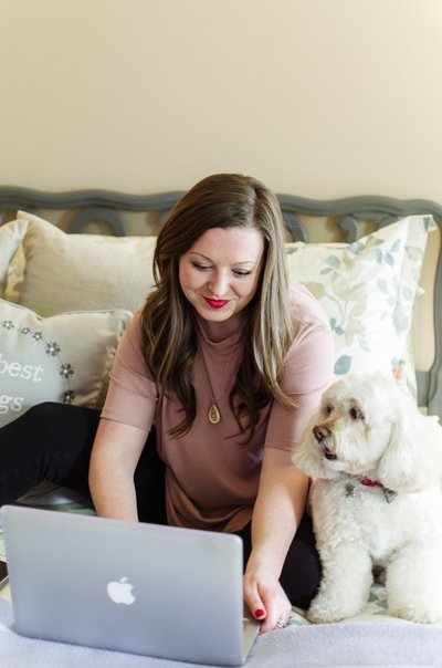 Business woman sitting on bed with laptop and her cockapoo