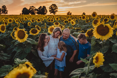 Family of five embracing at a sunflower field