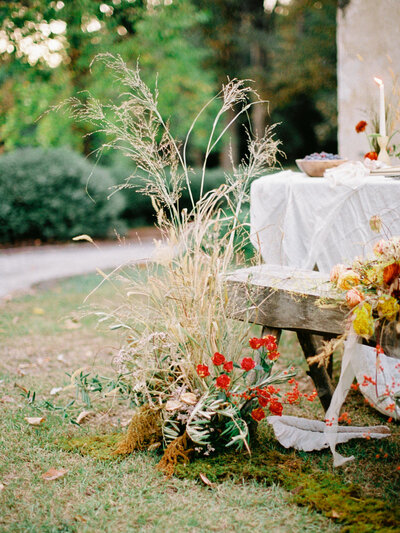 Wild and overgrown ground floral arrangement beside a dinner table for an autumn elopement at Wavering Place