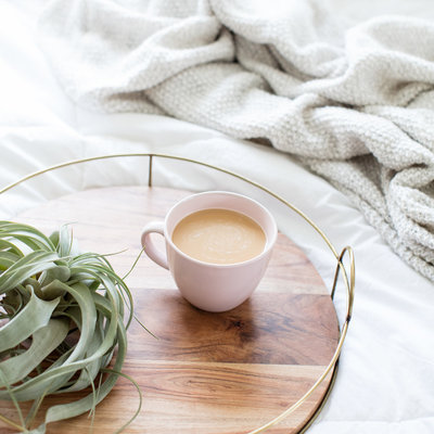 cup of coffee and air plant on a wooden tray on side of bed