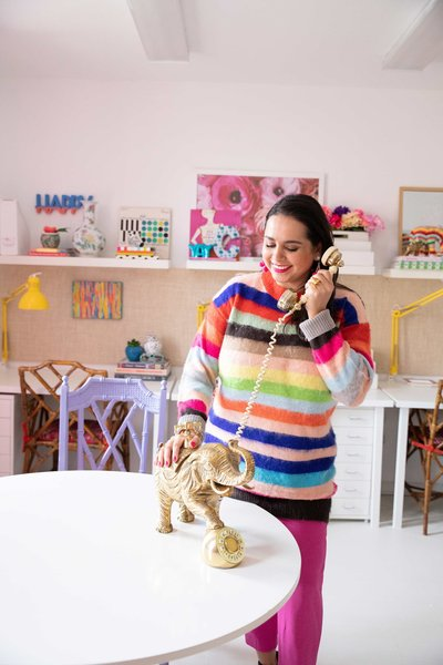 A woman in a rainbow sweater talking on a gold elephant telephone.