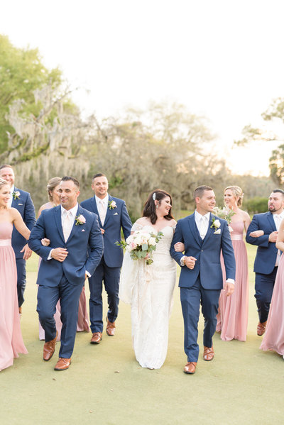 Bridal party walks and laughs together.