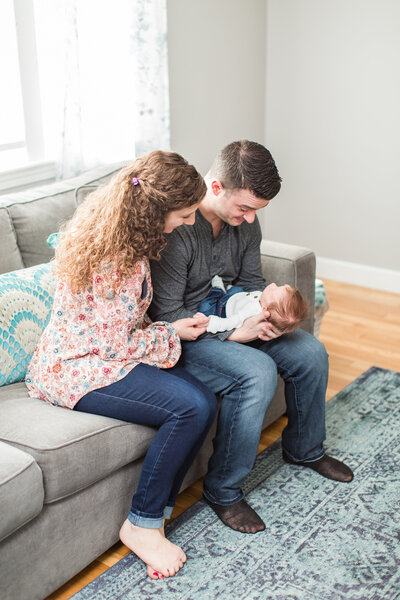 parents looking at newborn baby boy sitting on couch