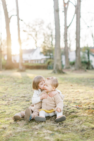 Toddler boy kisses baby girl's cheek in Maryland family session.