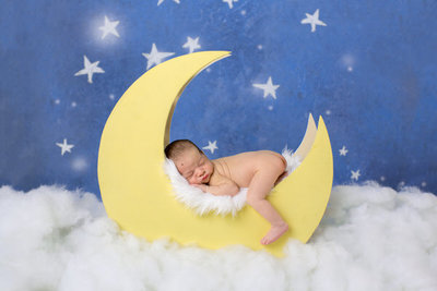 newborn boy asleep on moon prop